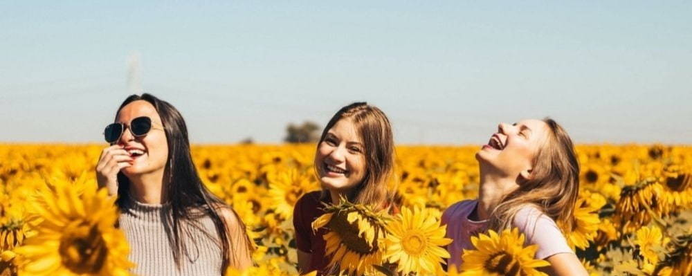 three young girls in a sunflower field